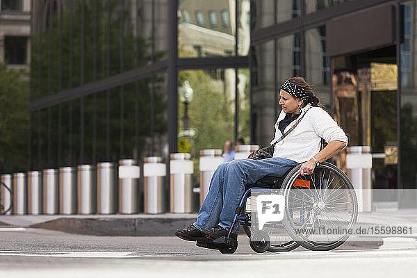 Woman with spinal cord injury crossing street  Boston  Massachusetts  USA