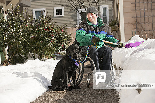 Woman with multiple sclerosis shoveling snow in a wheelchair with a service dog