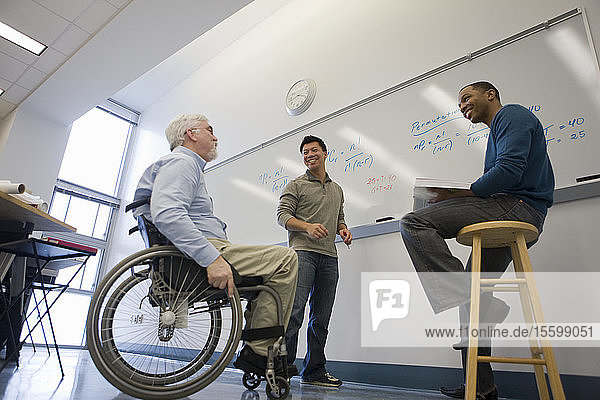University professor with Muscular Dystrophy talking with his students in a classroom