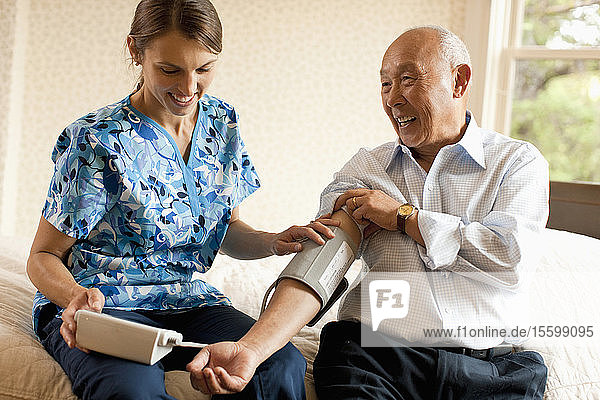 Senior man having his blood pressure checked by a nurse at home