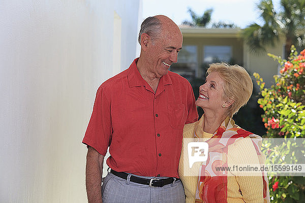 Senior couple standing at the doorway smiling at each other