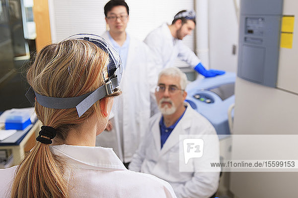 Professor and engineering students discussing bacteria culturing system in a laboratory