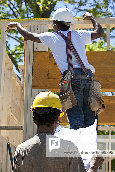 Construction workers measuring frame