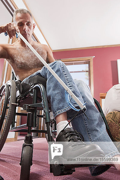 Man with spinal cord injury untying his shoes with an extension tool