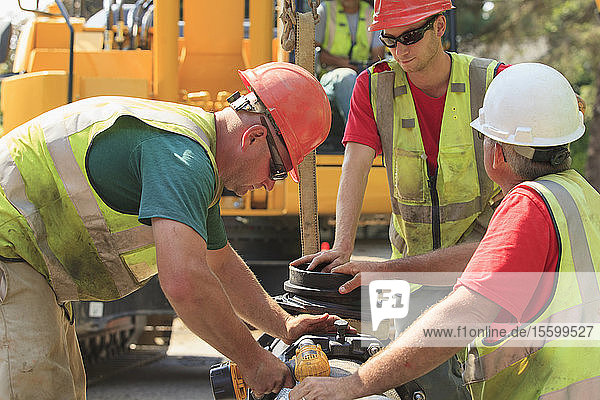 Construction workers using battery powered wrench to secure water main section with bolts