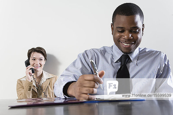 Business man in foreground with businesswoman using telephone in background.