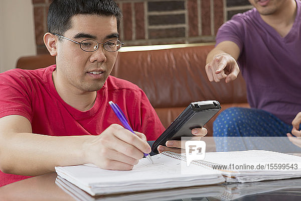 Asian man with Autism working on his homework with his brother