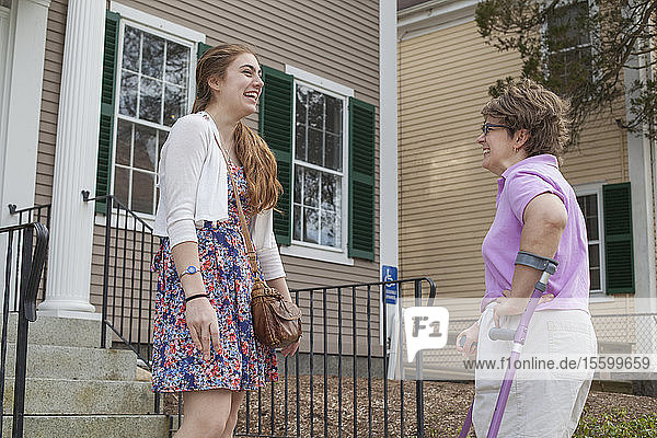 Woman with Cerebral Palsy talking with her sister in front of a house
