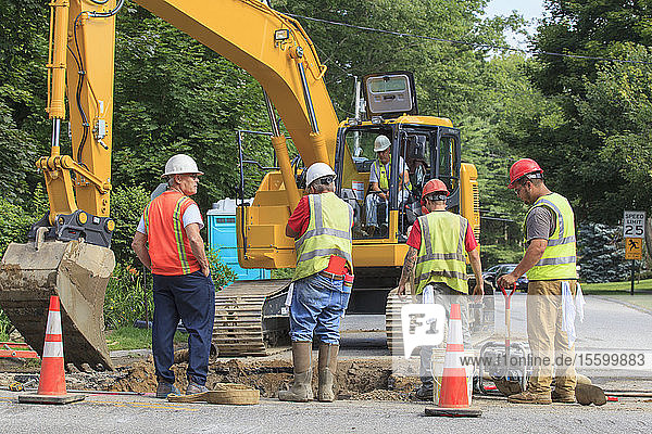 Construction workers digging hole to replace watermain