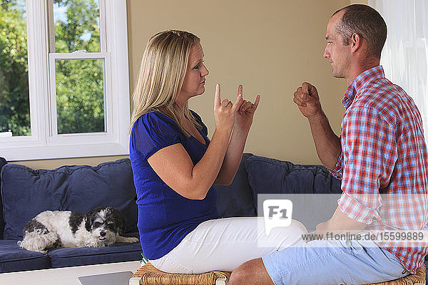Husband and wife with hearing impairments signing 'camping' in American sign language