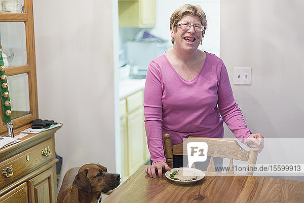 Woman with Autism standing near dining table and smiling