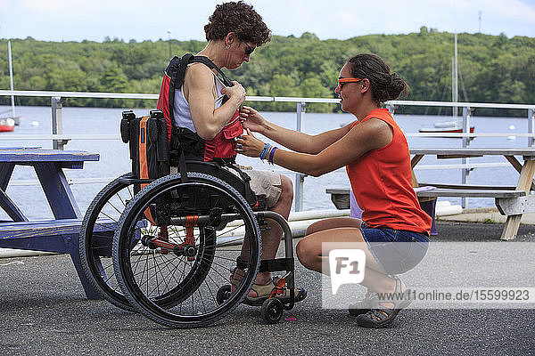 Woman with a Spinal Cord Injury being helped by an instructor to use a kayak