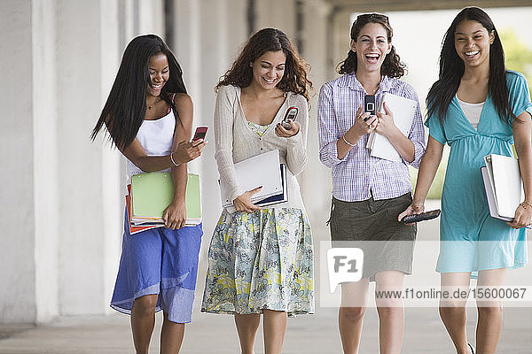 Female friends walking in university corridor and using mobile phones