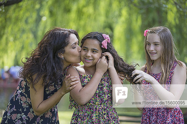 Happy Hispanic mother loving her two teen daughters with braces