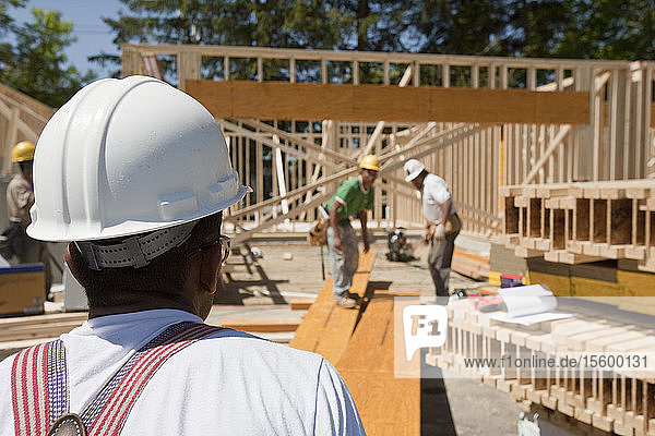 Carpenters working on a lamination beam at a construction site