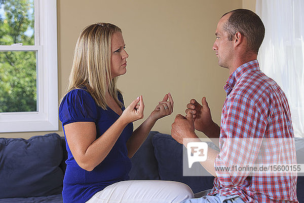 Husband and wife with hearing impairments signing 'what should we do' in American sign language