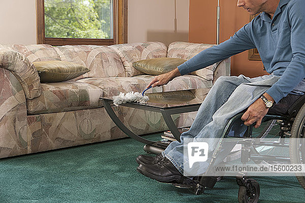 Man with spinal cord injury in a wheelchair dusting furniture