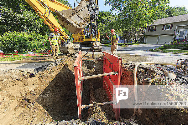 Construction worker placing shoring into hole with excavator