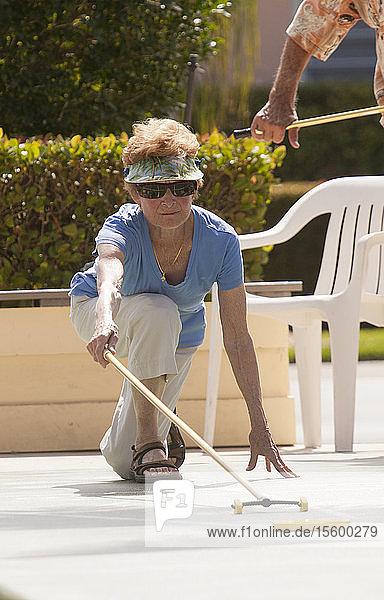 Senior woman playing shuffleboard