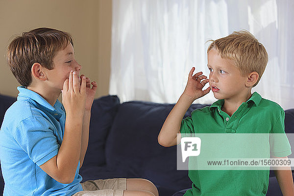Boys with hearing impairments signing 'cat' in American sign language on their couch