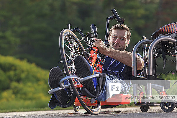 Man with spinal cord injury adjusting his feet on his custom adaptive hand cycle