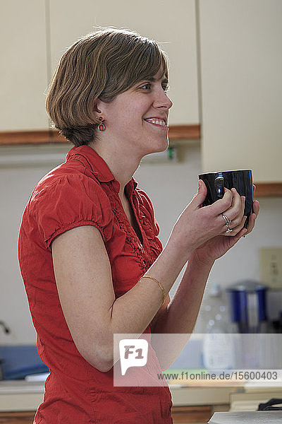 Young blind woman enjoying coffee in her kitchen