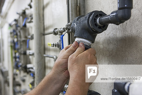 Engineer putting a rebuilt O2 electrochemical sensor probe into service on piping in water treatment plant