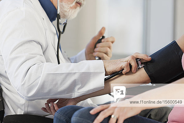 Doctor with Muscular Dystrophy checking the blood pressure of a patient