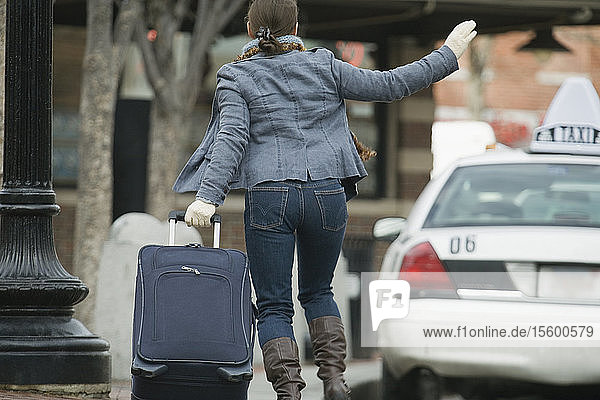 Rear view of a woman pulling her luggage and calling a taxi