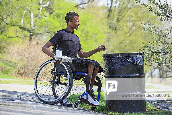 Man in a wheelchair who had Spinal Meningitis throwing away trash in a park