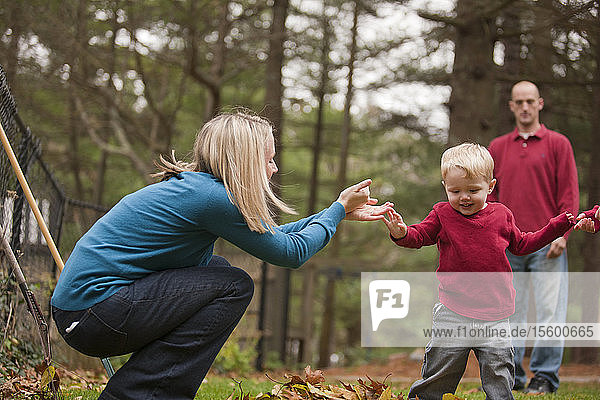 Woman signing the word 'Help' in American Sign Language while communicating with her son in a park