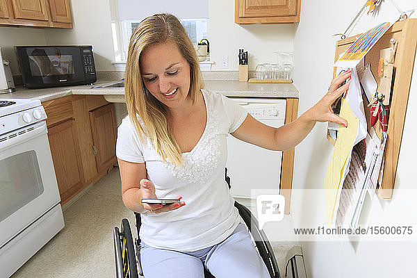 Woman with spinal cord injury in her accessible kitchen looking at her mobile phone