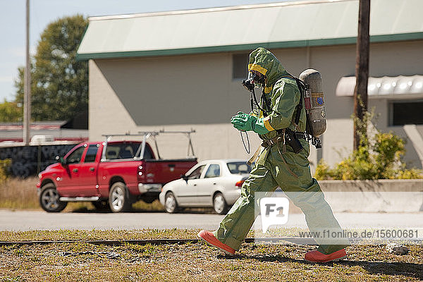 HazMat firefighter walking in a field with a camera
