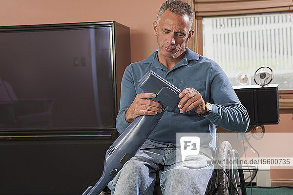 Man with spinal cord injury in a wheelchair cleaning a vacuum cleaner