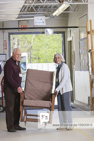 Senior couple moving furniture in a warehouse