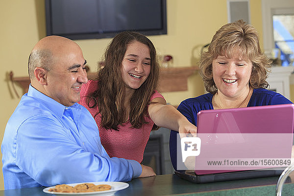 Daughter with father and mother laughing at laptop