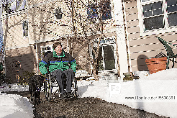 Woman with multiple sclerosis in a wheelchair with a service dog in front of home