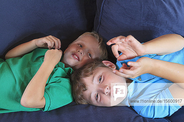 Boys with hearing impairments signing 'family' in American sign language on their couch