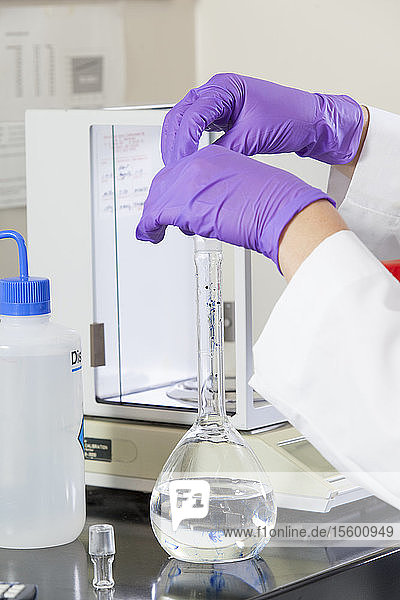 Laboratory scientist adding a precision amount of indigo into water sample flask