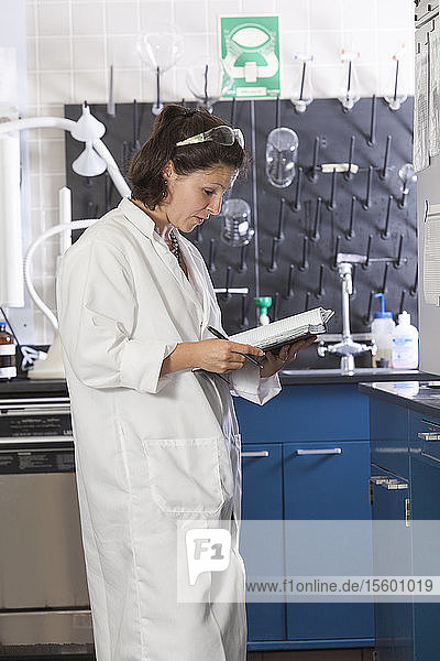 Laboratory scientist recording chemical analysis data in a laboratory