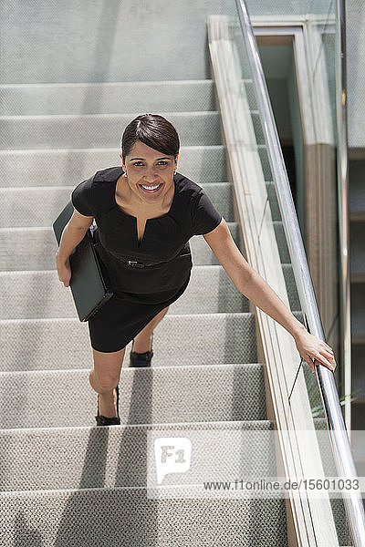 Hispanic businesswoman going up stairs of office building