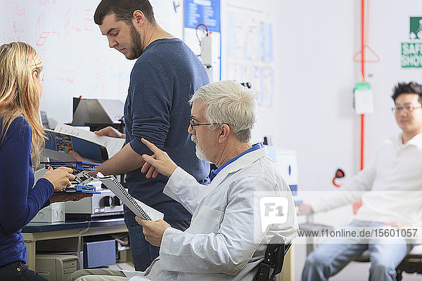Professor with muscular dystrophy and engineering students using manual to set up x-ray fluorescence experiment in a Laboratory
