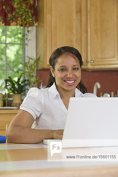 Hispanic businesswoman working on a laptop in the kitchen