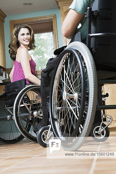 Side profile of a mid adult woman sitting in a wheelchair and smiling