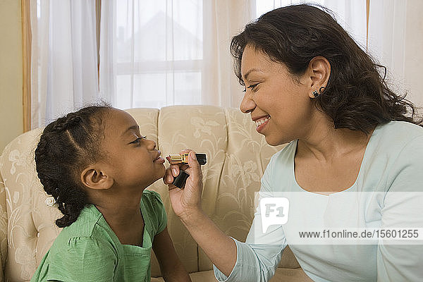 Hispanic woman applying lipstick on her daughter's lips