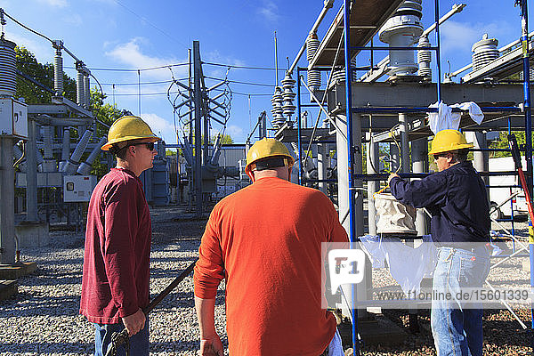 Power engineers working at high voltage power distribution station