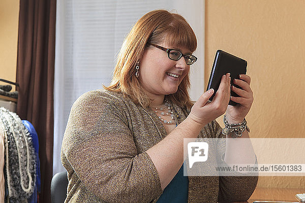 Woman who is legally blind using her tablet in her home