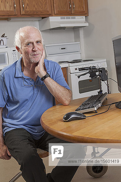 Portrait of a man with Ataxia relaxing at his computer in the kitchen