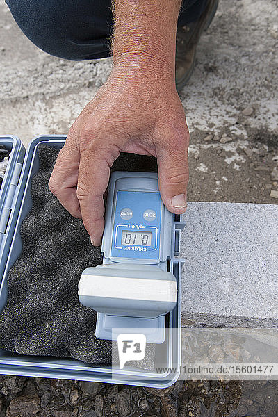 Engineer working with chlorine monitor in water sample kit