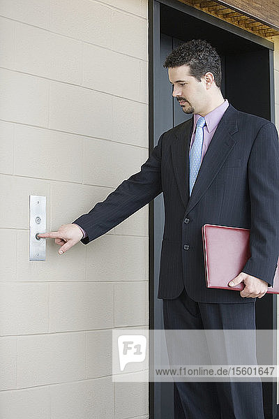 Businessman pressing button for elevator in an office building